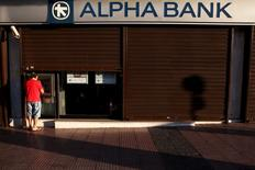 Devant une succursale d'Alpha Bank dans le centre d'Athènes. Les banques grecques vont être soumises au cours des prochains mois à des tests de résistance accélérés afin d'évaluer leurs besoins en capitaux frais, les autorités souhaitant boucler leur recapitalisation avant la fin de l'année. Ce nouvel examen réalisé par les autorités européennes et grecques sera achevé après l'été, selon une source bancaire. /Photo prise le 19 juillet 2015/REUTERS/Yiannis Kourtoglou