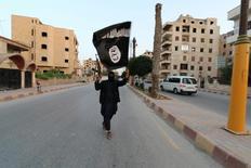 """Вооруженный мужчина с флагом """"Исламского государства""""  в Ракке, Сирия 29 июня 2014 года. Боевики египетского крыла экстремистской организации """"Исламское государство"""" опубликовали фото обезглавленного тела заложника-хорвата, которого группировка грозила убить на прошлой неделе, сообщил ресурс SITE в среду. REUTERS/Stringer"""