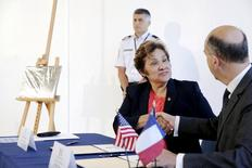 """U.S. Immigration and Customs Enforcement Director Sarah Saldana (2nd R) shakes hands with France's Deputy Chief of Mission Frederic Dore (R) after signing the certificate of transfer at an event to mark the repatriation of a stolen painting by Pablo Picasso entitled """"La Coiffeuse"""" at the French Embassy in Washington August 13, 2015.  REUTERS/Jonathan Ernst"""