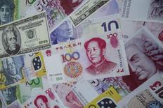 Рекламный постер у пункта обмена валюты в Гонконге. 13 августа 2015 года. Доллар достиг почти восьминедельного минимума к корзине валют в пятницу после появления очередных слабых данных из Китая, усиливших сомнения в том, что ФРС США сможет повысить ключевую ставку в сентябре. REUTERS/Tyrone Siu