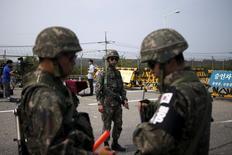 Южнокорейские солдаты на пропускном пункте при въезде на мост, ведущий в деревню Пханмунджом. 24 августа 2015 года. Северная и Южная Кореи договорились утром вторника положить конец военному противостоянию, которое привело к обмену артиллерийскими ударами и усилило напряжение на одной из наиболее укрепленных границ в мире. REUTERS/Kim Hong-Ji