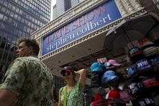 """People try on souvenir hats beneath the marquee for """"The Late Show with Stephen Colbert"""" at the Ed Sullivan Theater in Manhattan, New York, August 21, 2015. Colbert is set to host the show, which was previously presented by David Letterman. REUTERS/Andrew Kelly - RTX1P489"""