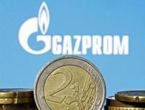 """Монеты евро на фоне логотипа Газпрома. Зеница, 21 апреля 2015 года. Газпром начал в понедельник экспортный аукцион по продаже 3,2 миллиарда кубометров газа, на котором среди 39 компаний зарегистрировались E.ON, Engie, Goldman Sachs и трейдинговая """"дочка"""" Новатэка Novatek Gas and Power, сказала перед началом торгов глава Газпромэкспорта Елена Бурмистрова. REUTERS/Dado Ruvic"""