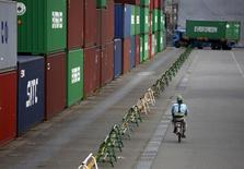 A worker rides a bicycle past containers at a port in Tokyo August 19, 2015. REUTERS/Issei Kato