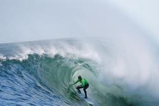 Shawn Dollar of the U.S. rides in a barrel during the final round of the Mavericks Invitational surfing competition in Half Moon Bay, California in this January 20, 2013 file photo. REUTERS/Stephen Lam/Files