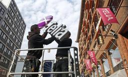 Рабочие устанавливают логотип TeliaSonera на здании, в котором расположен магазин компании, в Стокгольме 12 мая 2011 года. Шведская телекоммуникационная компания TeliaSonera заявила в четверг об инициировании процесса сокращения своего присутствия в Евразийском регионе с длинным планом по выходу из инвестиционных проектов, говорится в сообщении компании. REUTERS/Bob Strong