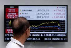 Un peatón mira un tablero electrónico que muestra la gráfica de fluctuación del índice Nikkei, el Dow Jones y el NASDAQ, afuera de una correduría en Tokio, Japón, 9 de septiembre de 2015. El índice Nikkei de la bolsa de Tokio cortó una racha de tres días de ganancias el viernes después de que la Reserva Federal mantuvo las tasas de interés en un mínimo histórico, aumentando las preocupaciones sobre la salud de la economía en Estados Unidos y el resto del mundo. REUTERS/Yuya Shino