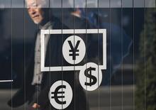Человек проходит мимо пункта обмена валюты в Токио 27 ноября 2014 года. Курс доллара снижается к иене и евро, и участники рынки обсуждают возможность смягчения политики центробанков после того, как ФРС не повысила процентные ставки. REUTERS/Issei Kato