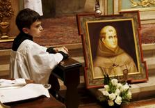 Altar server Shane Cleary kneels next to Friar Junipero Serra's grave during mass at the Carmel Mission Basilica in Carmel, California, September 23, 2015. REUTERS/Michael Fiala