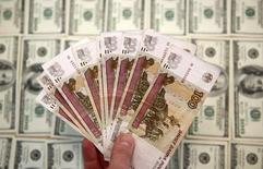 Рублевые и долларовые купюры в Сараево 9 марта 2015 года. Рубль начал торги четверга почти на неизменных уровнях, настраиваясь на консолидационное движение торговой сессии в ожидании более четких триггеров на фоне волатильных нефтяных фьючерсов. REUTERS/Dado Ruvic