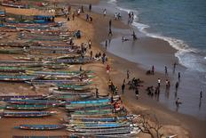 People are pictured on a beach next to fishing canoes in Dakar, Senegal, June 21, 2013. REUTERS/Joe Penney