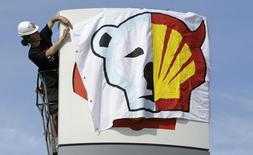 A Greenpeace environmental activist hangs a banner on a Shell gas station sign in Prague May 10, 2012.   REUTERS/David W Cerny