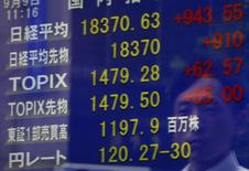 Un peatón se refleja en un tablero electrónico que muestra el índice Nikkei y otros índices de mercado, en una correduría en Tokio, Japón, 9 de septiembre de 2015. Las bolsas de Asia tocaron el miércoles máximos en siete semanas luego de que un repunte en los precios del petróleo impulsó a las acciones ligadas a las materias primas, y la confianza también fue apoyada cuando la surcoreana Samsung Electronics ofreció un pronóstico mejor que lo previsto de ganancias. REUTERS/Yuya Shino