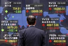 Пешеход у экрана с котировками в Токио 27 августа 2015 года. Азиатские фондовые рынки выросли, так как протокол совещания ФРС показал, что центробанк не спешит поднимать процентные ставки.  REUTERS/Yuya Shino
