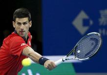 Novak Djokovic of Serbia hits a return against John Isner of U.S. during their men's singles match at the China Open tennis tournament in Beijing, China, October 9, 2015.    REUTERS/Kim Kyung-Hoon