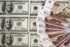 Рублевые и долларовые купюры в Сараево 9 марта 2015 года. Рубль вечером пятницы растерял преимущество из-за разворота в минус нефтяных котировок, но, тем не менее, формирует лучшую неделю 2015 года на фоне нефтяного ралли и снижения ожиданий повышения ставки ФРС в текущем году. REUTERS/Dado Ruvic