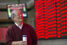 An investor looks at an electronic board showing stock information at a brokerage house in Nanjing, Jiangsu province, China, October 12, 2015.   REUTERS/China Daily
