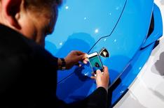 A visitor takes a picture of the logo on the Lamborghini Huracan LP 610-4 Spyder during the Volkswagen group night ahead of the Frankfurt Motor Show (IAA) in Frankfurt, Germany, September 14, 2015. REUTERS/Kai Pfaffenbach
