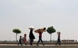 Сирийские беженцы идут к пропускному пункту в Акчакале, чтобы вернуться на родину. 17 июня 2015 года. Европейский союз может выделить Турции 3 миллиарда евро, а также готов к смягчению визового режима и новым переговорам о вступлении страны в блок, в обмен на помощь в решении проблемы наплыва мигрантов. REUTERS/Umit Bektas