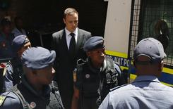 South African Olympic and Paralympic sprinter Oscar Pistorius (C ) is escorted to a police van after his sentencing at the North Gauteng High Court in Pretoria October 21, 2014. Pistorius was sentenced to five years in prison on Tuesday for killing his girlfriend Reeva Steenkamp, ending a trial that has gripped South Africa and the world. REUTERS/Siphiwe Sibeko (SOUTH AFRICA - Tags: SPORT CRIME LAW ATHLETICS TPX IMAGES OF THE DAY) - RTR4AYRN