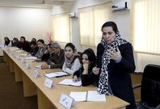An Afghan woman speaks as they attend a class of the gender and women's studies masters program in Kabul University, Afghanistan October 19, 2015.  REUTERS/Mohammad Ismail