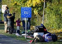Мигранты на границе Словении и Австрии близ деревни Шпильфельд. 24 октября 2015 года. Страны ЕС, которые докажут, что несут чрезвычайные расходы из-за кризиса с беженцами, получат бюджетные послабления, сообщил глава Еврокомиссии Жан-Клод Юнкер во вторник. REUTERS/Leonhard Foeger