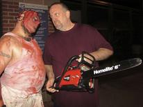 "Ted Corcoran (R) of Oklahoma City stands outside the Bricktown Haunted Warehouse with ""chainsaw guy"" actor Marcus ""Panda"" Bagwell (L) in Oklahoma City, Oklahoma October 25, 2015. REUTERS/Heide Brandes"