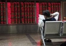 Un inversor lee un diario frente a un tablero electrónico que muestra la información de las acciones, en una correduría en Pekín, China, 29 de octubre de 2015. Las acciones chinas subieron el jueves mientras los inversores esperaban la publicación de los objetivos de crecimiento para el decimotercer Plan Quinquenal, que se esperan más tarde en el día después de las deliberaciones del Comité Central del Partido Comunista de China. REUTERS/Li Sanxian