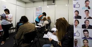 Personas rellenando formularios de empleo en Sao Paulo. 11 de mayo de 2015. La tasa de desempleo en Brasil subió a un 8,7 por ciento en el trimestre hasta agosto y marcó un nuevo nivel histórico de la serie iniciada en 2012, según el sondeo Pnad divulgado el jueves por el estatal Instituto Brasileño de Geografía y Estadística (IBGE). REUTERS/Paulo Whitaker