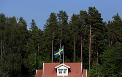 The Swedish national flag flies in front of a house near the town of Sodertalje, south west of Stockholm, Sweden, in this June 5, 2014 file photo.  REUTERS/Cathal McNaughton/Files