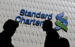 Standard Chartered va augmenter son capital de 5,1 milliards de dollars (4,6 milliards d'euros) et supprimer 15.000 emplois dans le cadre d'un plan stratégique destiné à restaurer sa profitabilité. /Photo d'archives/REUTERS/Bobby Yip