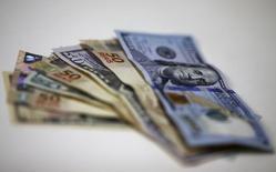Notas de dólar e real vistas em casa de câmbio no Rio de Janeiro.   10/09/2015    REUTERS/Ricardo Moraes