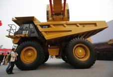 Un hombre junto a un camión de Caterpillar en una exposición minera en Pekín, oct 22, 2013.  La canadiense Finning International Inc, la mayor distribuidora de equipos Caterpillar Inc del mundo, dijo el jueves que recortará otros 1.100 puestos de trabajo en Canadá y América del Sur, además de cerrar 11 tiendas locales por bajas ventas. REUTERS/Kim Kyung-Hoon