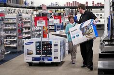 An employee helps a customer with a television at a Best Buy store in Denver May 14, 2015.    REUTERS/Rick Wilking