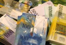 Банкноты евро и швейцарского франка в отделении банка в Берне. 25 ноября 2014 года. Золотовалютные резервы РФ составили на конец прошлой недели $364,1 миллиарда, потеряв $2,0 миллиарда из-за отрицательной переоценки входящих в их структуру активов, о чем отчитался Банк России на своем сайте. REUTERS/Ruben Sprich