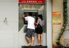 Una pareja utilizando un cajero automático a las afueras de un banco en Pekín, ago 19, 2015. Algunos bancos chinos, afectados por un incremento de préstamos impagos en una economía debilitada, no están reconociendo que hayan impactado sus libros para evitar tener que desembolsar capital.      REUTERS/David Gray