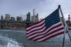 Vista de una bandera de Estados Unidos con el Puente de Manhattan y el One World Trade Center, en Nueva York, 21 de septiembre de 2015. El crecimiento económico de Estados Unidos en el tercer trimestre fue mayor de lo que se había estimado inicialmente, sugiriendo una resistencia que podría dar más confianza a la Reserva Federal para subir las tasas de interés el próximo mes. REUTERS/Darren Ornitz