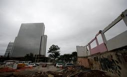 Construction work of the Olympic Main Press Center for the Rio 2016 Olympic Park is seen near a partially demolished house in the Vila Autodromo slum in Rio de Janeiro, Brazil, November 23, 2015.  REUTERS/Sergio Moraes