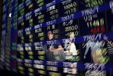Transeúntes se reflejan en un tablero electrónico que muestra la información de las acciones, afuera de una correduría en Tokio, 25 de agosto de 2015. Las acciones chinas cayeron el viernes, lastrando a otros mercados bursátiles de Asia, luego de que una nueva ofensiva regulatoria de Pekín y unas ganancias industriales débiles minaron la confianza de los inversores. REUTERS/Issei Kato
