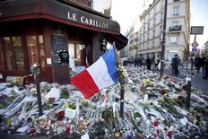 """A French flag flies over flowers, candles and messages in tribute to victims outside """"Le Carillon"""" restaurant a week after a series of deadly attacks in the French capital Paris, France, November 22, 2015. REUTERS/Charles Platiau"""