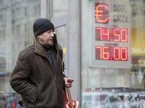 Мужчина у пункта обмена валюты в Москве. 11 февраля 2015 года. Рубль ушел в минус к вечеру вторника после умеренного роста утром и днем, копируя динамику нефти Brent, которая после попыток коррекции вновь развернулась вниз и впервые с марта 2009 года побывала ниже психологической отметки $40 за баррель. REUTERS/Sergei Karpukhin
