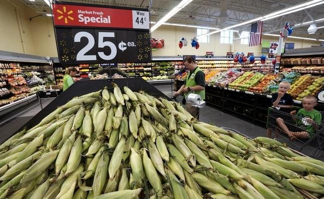 An employee works in the fresh produce department with a mound of sweet corn at the Wal-Mart Supercenter in Springdale, Arkansas, June 4, 2015. REUTERS/Rick Wilking