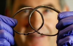 Silver arm-rings are held by metal-detectorist, James Mather, who discovered a Viking Hoard, which also included silver ingots and rare coins of King Alfred of Wessex and King Ceolwulf II of Mercia, at the British Museum London Britain December 10, 2015. REUTERS/Peter Nicholls
