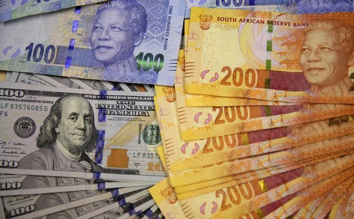South African bank notes featuring images of former South African President Nelson Mandela (R) are displayed next to the American dollar notes in this photo illustration in Johannesburg in a file photo. REUTERS/Siphiwe Sibeko