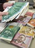 Кассир пересчитывает киргизские сомы в Бишкеке 19 февраля 2010 года. S&P впервые присвоило Киргизии кредитный рейтинг - B/B в иностранной и местной валютах, со стабильным прогнозом - ожидая прежней политики благодаря сохранению власти у правящей партии после недавних выборов и подчеркнув зависимость экономики от России. REUTERS/Vladimir Pirogov