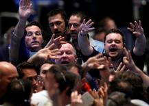 Traders in the 30-year bond options pit at the Chicago Board of Trade signal orders, November 3, 2010. REUTERS/Frank Polich