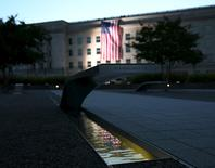 A United States flag is reflected at the 9/11 Memorial after being unfurled at sunrise at the Pentagon in Washington September 11, 2015. REUTERS/Gary Cameron