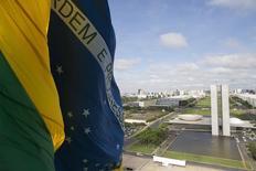 La bandera de Brasil, con en el Congreso Nacional en el fondo, 19 de noviembre de 2014. El Congreso de Brasil aprobó el jueves una reducción en el objetivo de ahorro fiscal del país para 2016, pero rechazó una petición de la presidenta Dilma Rousseff para efectuar un recorte mayor que generó dudas sobre su compromiso en la contención del creciente déficit. REUTERS / Ueslei Marcelino