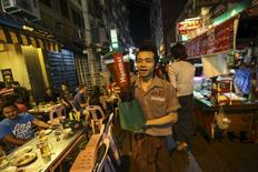 A waiter carries a tower of Myanmar beer in 19th street, also known as Yangon beer street in Yangon December 8, 2015. REUTERS/Soe Zeya Tun