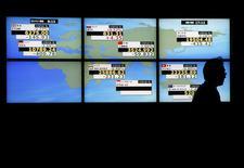Un hombre camina junto a un tablero electrónico que muestra los índices de mercado de varios países, afuera de una correduría en Tokio, Japón, 4 de diciembre de 2015. Las acciones chinas lideraban un repunte de los mercados de Asia el lunes y el precio del crudo Brent se desplomó a mínimos en 11 años por los temores renovados sobre un exceso de la oferta mundial de petróleo. REUTERS/Toru Hanai